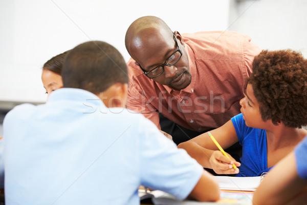 Professor ajuda alunos estudar sala de aula menina Foto stock © monkey_business