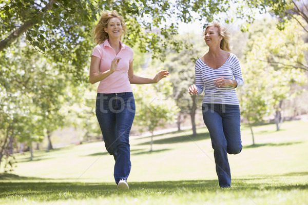 Two women running in park and smiling Stock photo © monkey_business