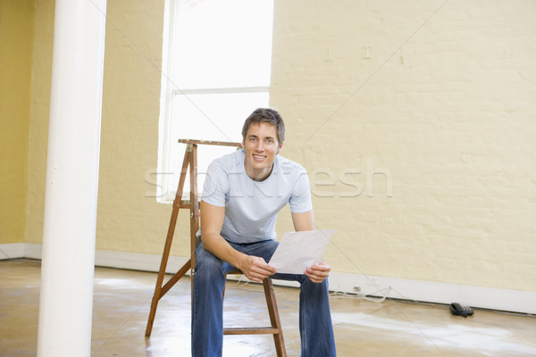 Man sitting on ladder in empty space holding paper smiling Stock photo © monkey_business