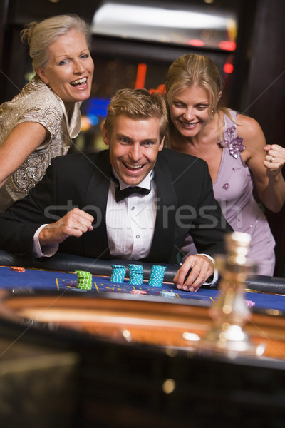 Man winning at roulette table surrounded by glamorous women Stock photo © monkey_business