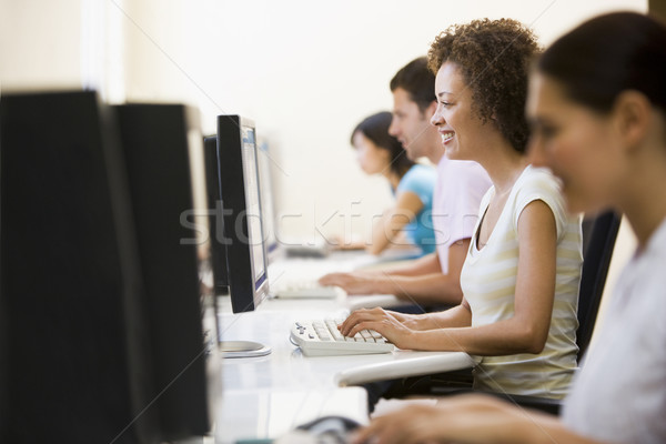Quatre personnes salle informatique tapant souriant femme bureau Photo stock © monkey_business