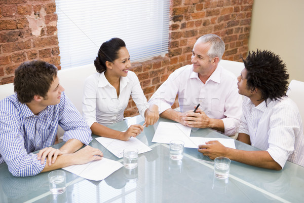 Four businesspeople in boardroom smiling Stock photo © monkey_business