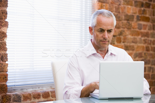 Businessman in office looking at laptop Stock photo © monkey_business