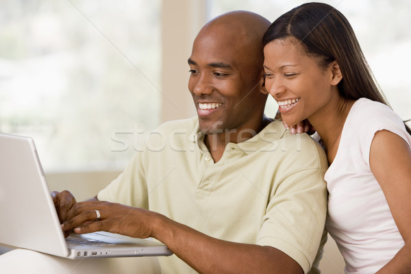 Couple in living room using laptop and smiling Stock photo © monkey_business