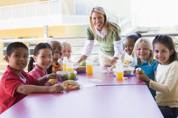 Kindergarten teacher supervising children eating lunch Stock photo © monkey_business