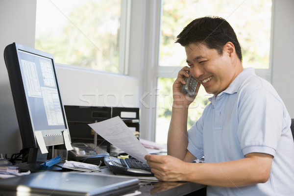 Man in home office with computer and paperwork on telephone smil Stock photo © monkey_business