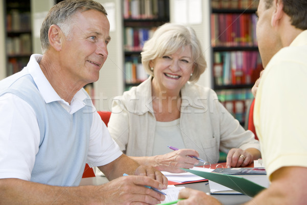 Stock photo: Adult students working together in a library