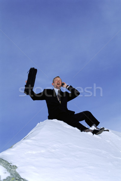 Businessman outdoors on snowy mountain using cellular phone and  Stock photo © monkey_business