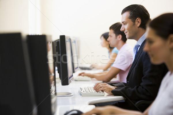 четыре человека сидят компьютерный зал набрав один человека Сток-фото © monkey_business