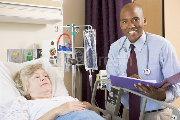 Doctor Making Notes About Senior Woman Lying In Hospital Bed Stock photo © monkey_business
