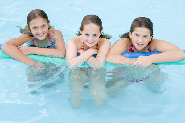 Three young girl friends in swimming pool with pool noodle smili Stock photo © monkey_business