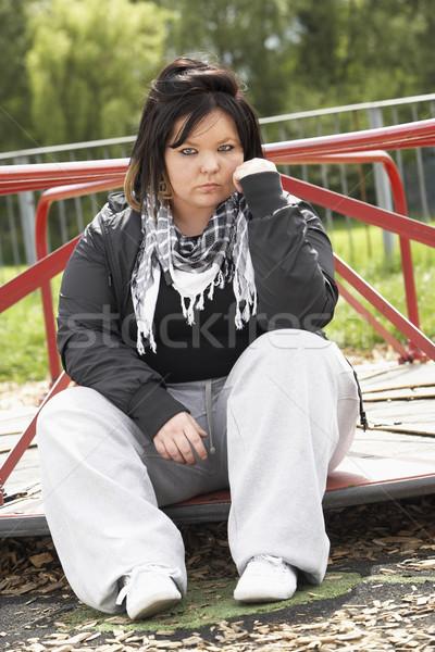 Jeune femme séance aire de jeux femme rue triste Photo stock © monkey_business