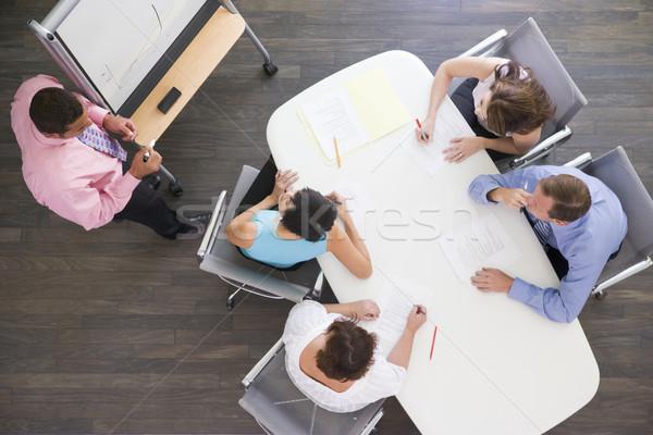 Four businesspeople at boardroom table watching presentation Stock photo © monkey_business