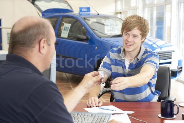 Moço enchimento papelada carro sala de exposição financiar Foto stock © monkey_business