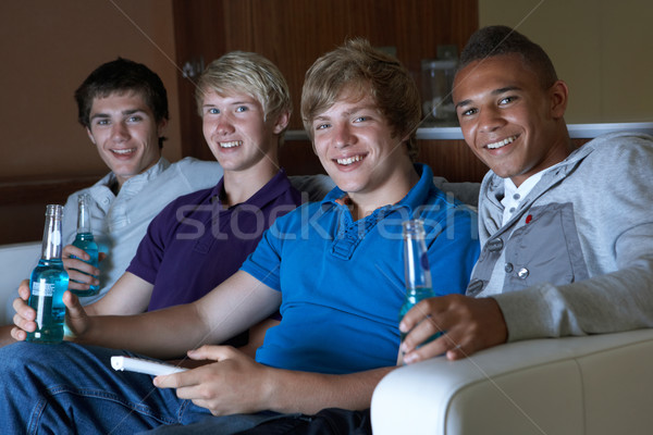 Group Of Teenage Boys Sitting On Sofa At Home Watching Drinking  Stock photo © monkey_business