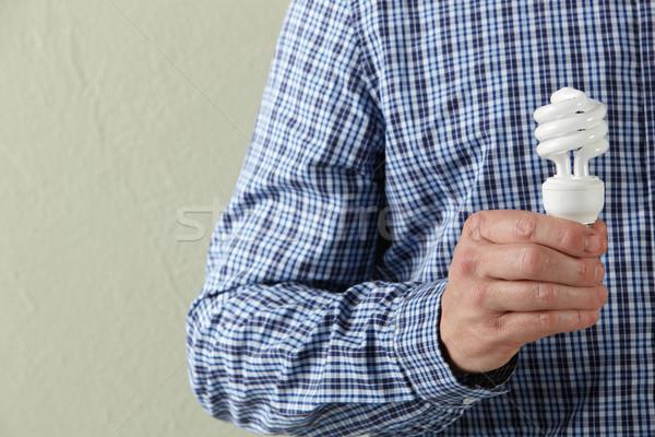 Cropped Studio Shot Of Man Holding Energy Saving Lightbulb Stock photo © monkey_business