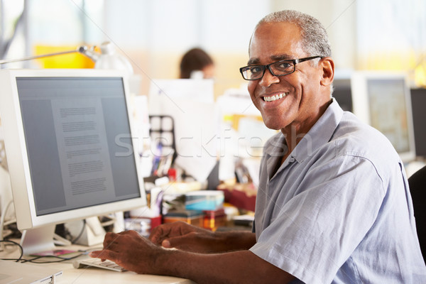 Man Working At Desk In Busy Creative Office Stock photo © monkey_business