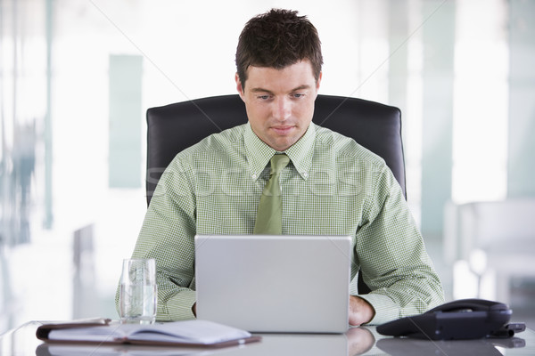 Businessman sitting in office with personal organizer and laptop Stock photo © monkey_business