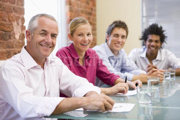 Négy üzletemberek tárgyaló mosolyog asztal üzletemberek Stock fotó © monkey_business