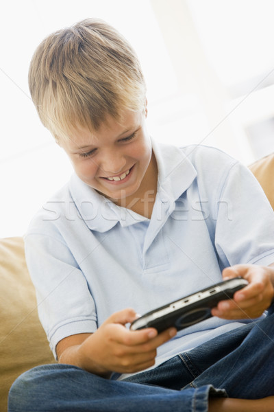 Young boy in living room with handheld video game smiling Stock photo © monkey_business