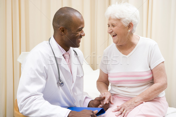 Doctor giving checkup to woman in exam room smiling Stock photo © monkey_business
