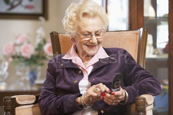 Idős nő sms üzenetküldés idős személy mosolyog Stock fotó © monkey_business