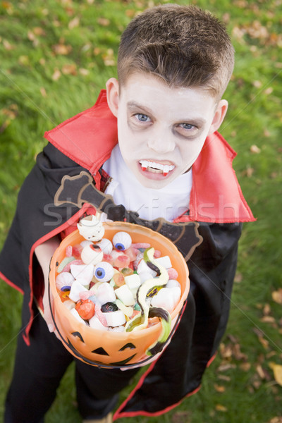 Young boy outdoors wearing vampire costume on Halloween holding  Stock photo © monkey_business