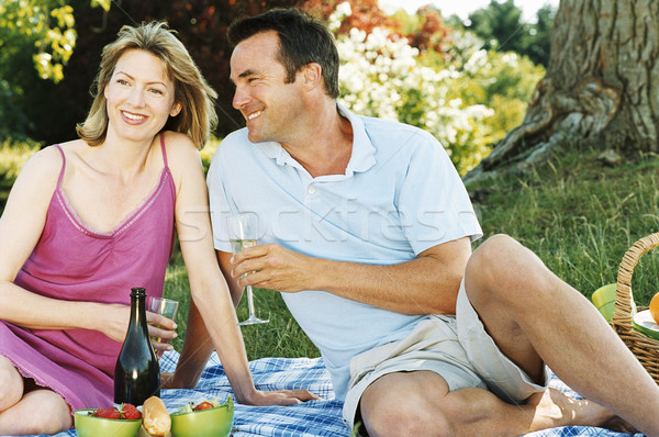 Stock photo: Couple sitting outdoors with picnic smiling