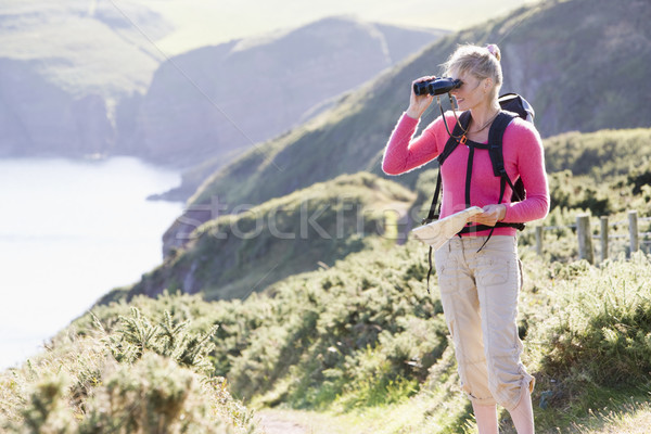Woman on cliffside path using binoculars Stock photo © monkey_business