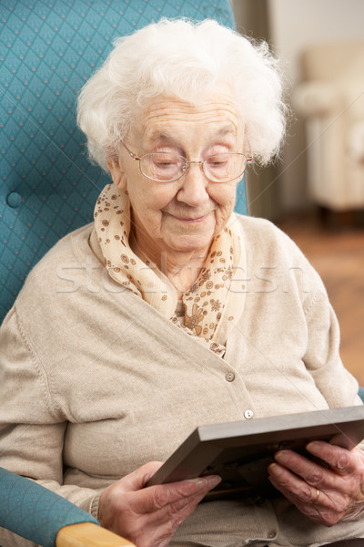 Sad Senior Woman Looking At Photograph In Frame Stock photo © monkey_business