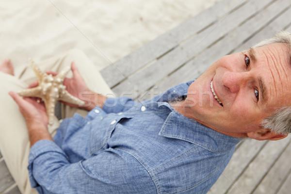 Senior man holding starfish Stock photo © monkey_business