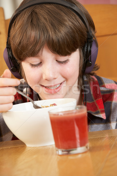 Boy Listening To MP3 Player Whilst Eating Breakfast Stock photo © monkey_business