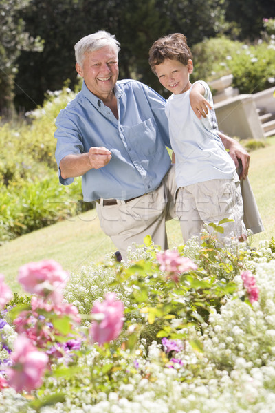 Grandfather and grandson outdoors in garden pointing at plants a Stock photo © monkey_business