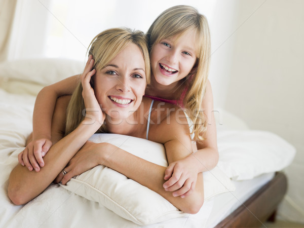 Woman and young girl lying in bed smiling Stock photo © monkey_business