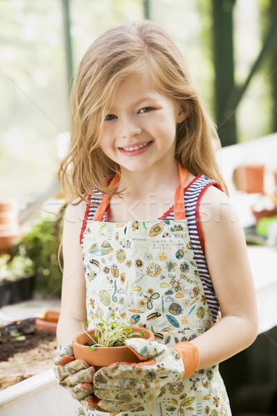 Young girl in greenhouse holding potted plant smiling Stock photo © monkey_business
