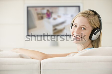 Man in living room watching television and wearing headphones Stock photo © monkey_business