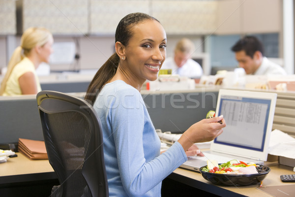 Businesswoman in cubicle with laptop eating salad Stock photo © monkey_business
