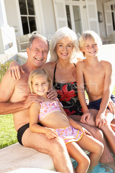 Portrait grands-parents petits enfants séance ensemble piscine Photo stock © monkey_business