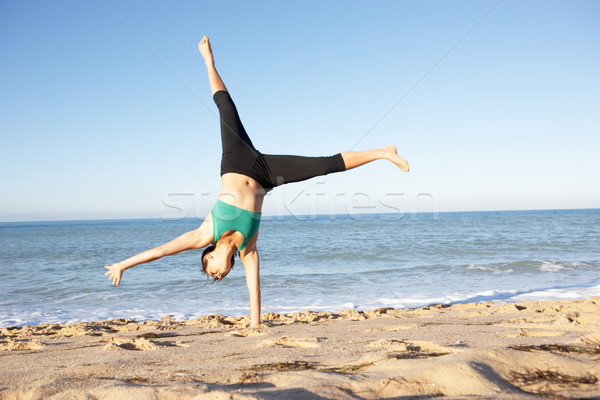 Young Woman In Fitness Clothing Turning Cartwheel On Beach Stock photo © monkey_business