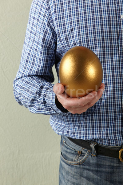 Cropped Studio Shot Of Man Holding Golden Egg Stock photo © monkey_business