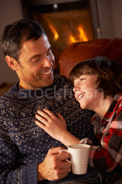 Father And Son Relaxing With Hot Drink By Cosy Log Fire Stock photo © monkey_business