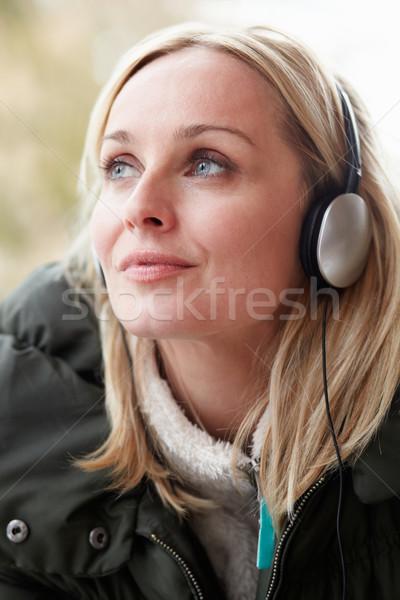 Nő visel fejhallgató zenét hallgat tél ruházat Stock fotó © monkey business eabf23a563