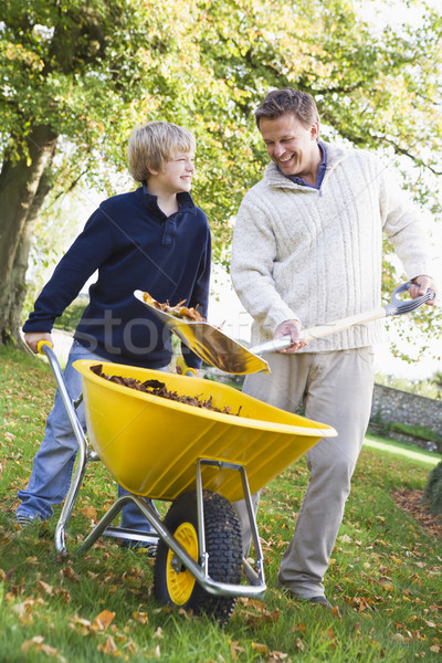 Son helping father collect leaves Stock photo © monkey_business