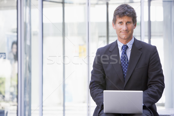 Businessman sitting in office lobby using laptop smiling Stock photo © monkey_business