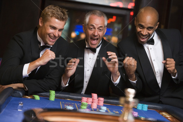 Group of men celebrating win at roulette table Stock photo © monkey_business
