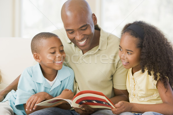 Man and two children sitting in living room reading book and smi Stock photo © monkey_business
