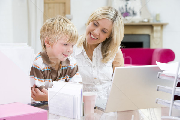 Woman and young boy in home office with laptop smiling Stock photo © monkey_business
