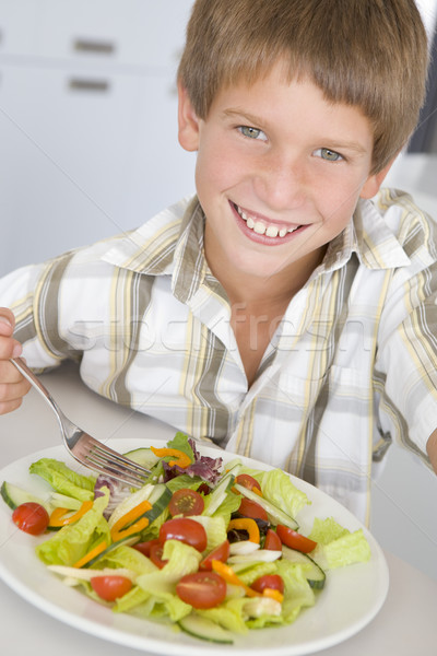 Young boy in kitchen eating salad smiling Stock photo © monkey_business