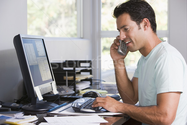 Man in home office on telephone using computer and smiling Stock photo © monkey_business