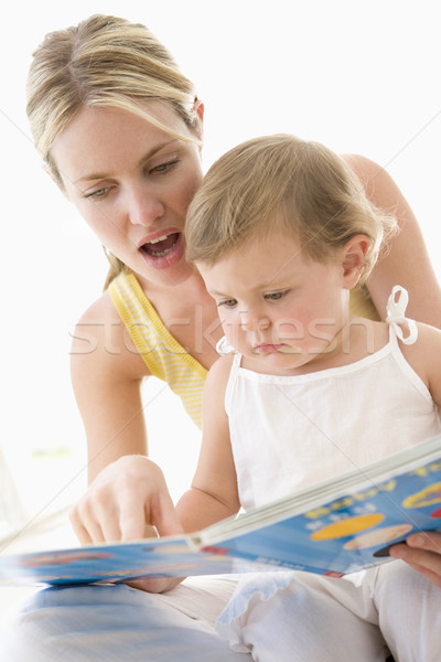 Mother and baby reading book indoors and pointing Stock photo © monkey_business